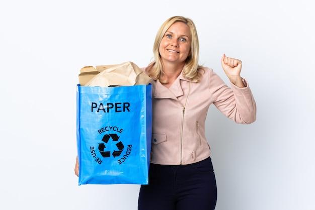 Donna di mezza età che tiene un sacchetto di riciclaggio pieno di carta da riciclare isolato su bianco che celebra una vittoria nella posizione del vincitore Foto Premium
