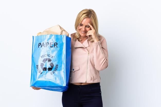 Donna di mezza età che tiene un sacchetto di riciclaggio pieno di carta da riciclare isolata sulla risata bianca Foto Premium