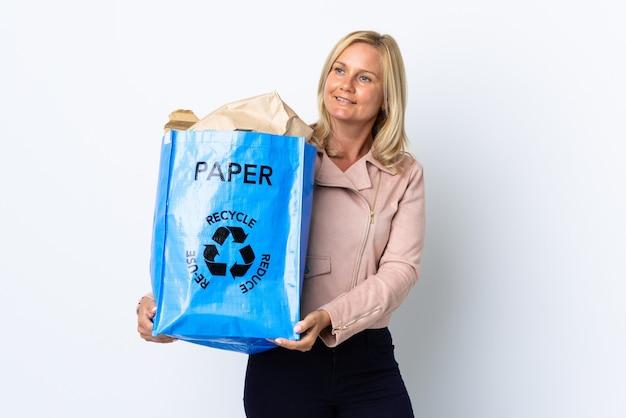 Donna di mezza età che tiene un sacchetto di riciclaggio pieno di carta da riciclare isolato su bianco che osserva al lato e sorridente Foto Premium