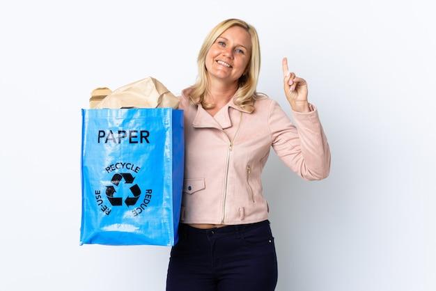 Donna di mezza età che tiene un sacchetto di riciclaggio pieno di carta da riciclare isolato su bianco rivolto verso l'alto una grande idea Foto Premium