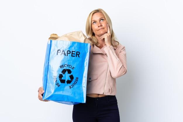 Donna di mezza età che tiene un sacchetto di riciclaggio pieno di carta da riciclare isolato su bianco pensando un'idea mentre osservava Foto Premium