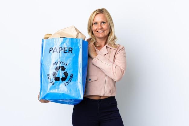 Donna di mezza età che tiene un sacchetto di riciclaggio pieno di carta da riciclare isolato sul muro bianco che celebra una vittoria Foto Premium