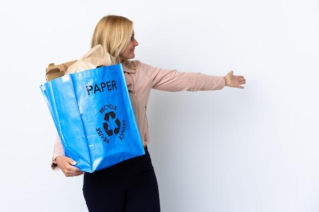 Donna di mezza età che tiene un sacchetto di riciclaggio pieno di carta da riciclare isolato sul muro bianco che estende le mani di lato per invitare a venire Foto Premium