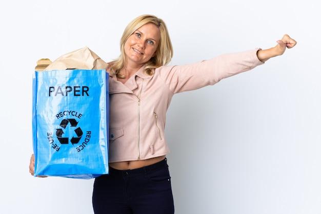 Donna di mezza età che tiene un sacchetto di riciclaggio pieno di carta da riciclare isolato sulla parete bianca che dà un pollice in alto gesto Foto Premium