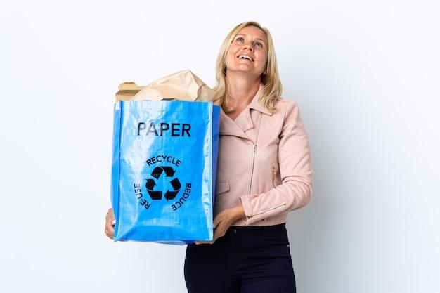 Donna di mezza età che tiene un sacchetto di riciclaggio pieno di carta da riciclare isolato sul muro bianco che ride in posizione laterale Foto Premium
