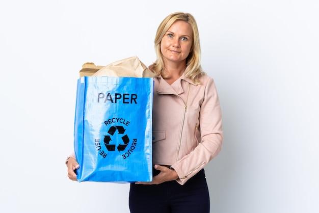 Donna di mezza età che tiene un sacchetto di riciclaggio pieno di carta da riciclare isolato sul muro bianco che guarda al lato Foto Premium