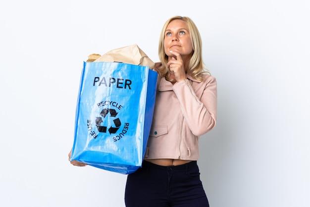 Donna di mezza età che tiene un sacchetto di riciclaggio pieno di carta da riciclare isolato sul muro bianco e alzando lo sguardo Foto Premium