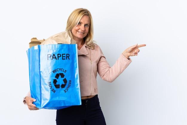 Donna di mezza età che tiene un sacchetto di riciclaggio pieno di carta da riciclare isolato sul muro bianco che punta il dito di lato Foto Premium