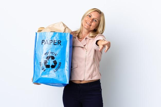 Donna di mezza età che tiene un sacchetto di riciclaggio pieno di carta da riciclare isolato sul muro bianco rivolto verso la parte anteriore con felice espressione Foto Premium