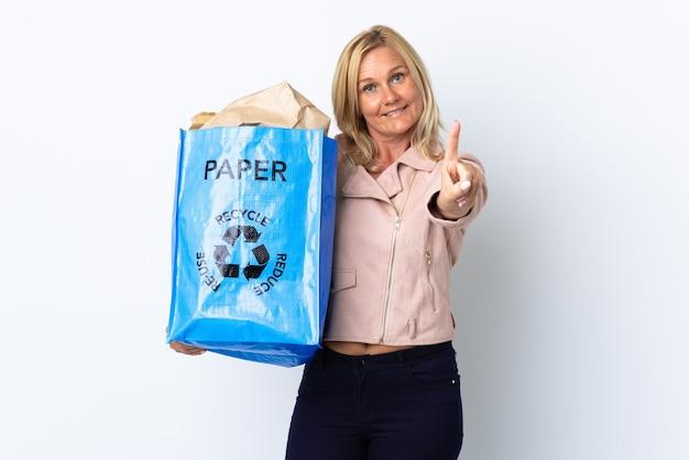 Donna di mezza età che tiene un sacchetto di riciclaggio pieno di carta da riciclare isolato sulla visualizzazione della parete bianca e alzando un dito Foto Premium