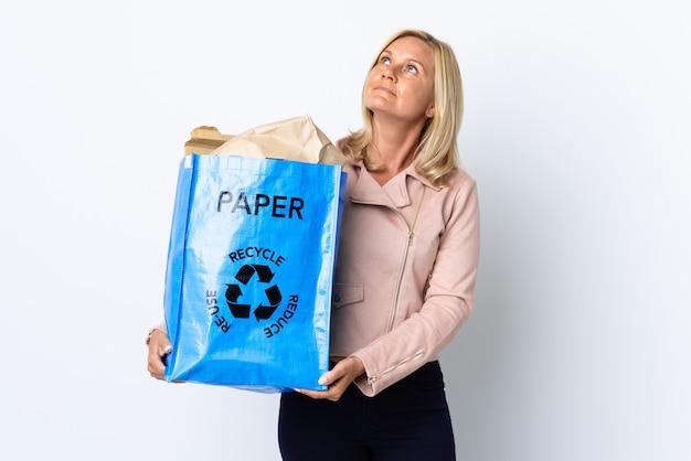 Donna di mezza età che tiene un sacchetto di riciclaggio pieno di carta da riciclare isolato sul muro bianco che pensa un'idea mentre osserva in su Foto Premium