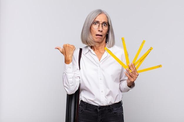 Donna di mezza età che guarda sbalordita incredula, indicando un oggetto sul lato e dicendo wow, incredibile. concetto di architetto Foto Premium