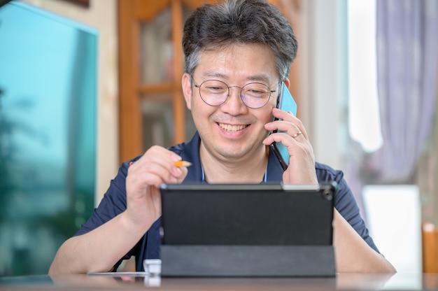 Uomo asiatico di mezza età che lavora a casa. concetto di telelavoro. Foto Premium
