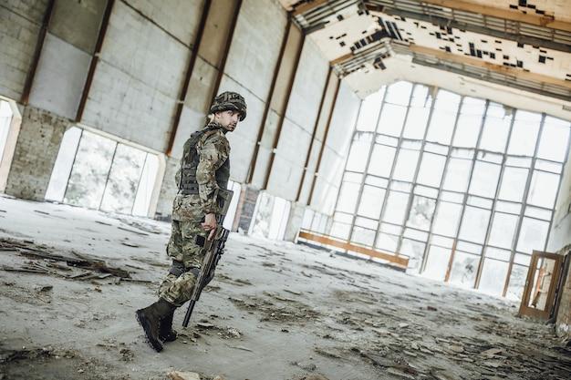Operazione di ricognizione militare. un giovane soldato con un grosso fucile in mano attraversa un edificio crollato, una vista da dietro! Foto Premium