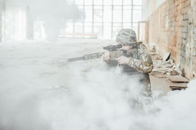 Il soldato militare in divisa tiene tra le mani un fucile moderno, punta nel fumo. Foto Premium