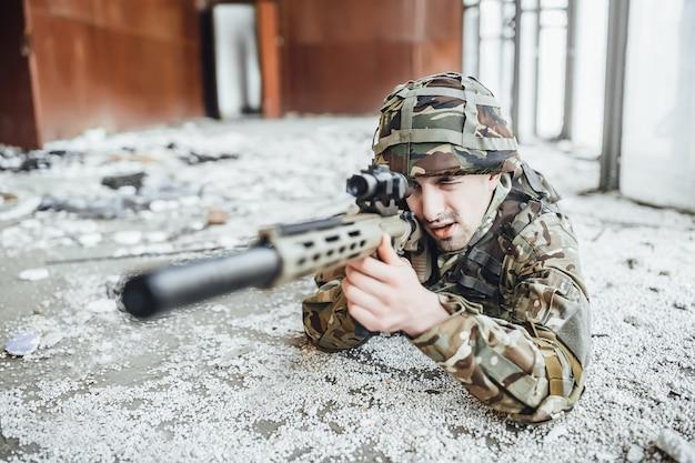 Il militare in divisa giace a terra e tiene in mano un grosso fucile Foto Premium