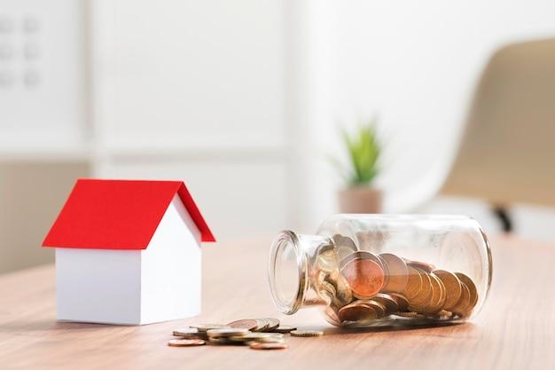 Banca miniatura con le monete in barattolo accanto Foto Premium