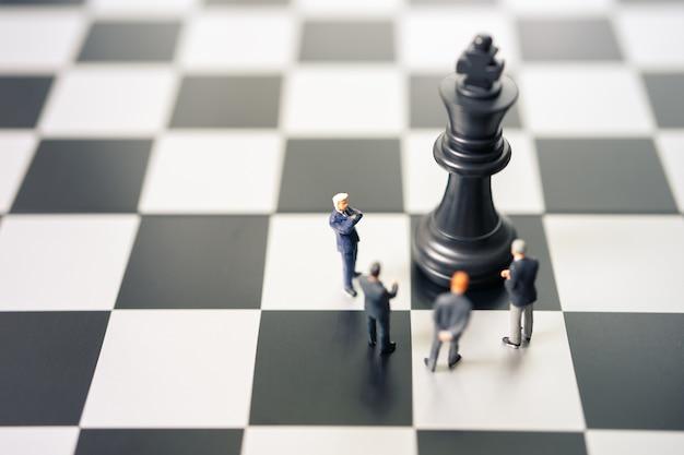 Uomini d'affari in miniatura persone in piedi su una scacchiera con un pezzo degli scacchi Foto Premium