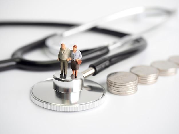 Persone in miniatura in piedi su stetoscopio medico con pila di monete. Foto Premium