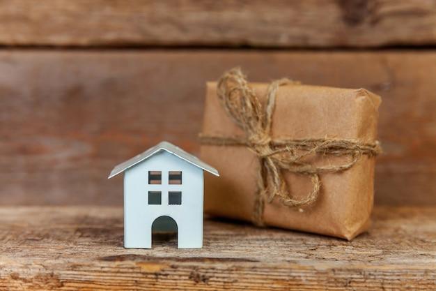 Miniatura casa giocattolo bianco e confezione regalo avvolto carta artigianale su sfondo di legno vecchio Foto Premium
