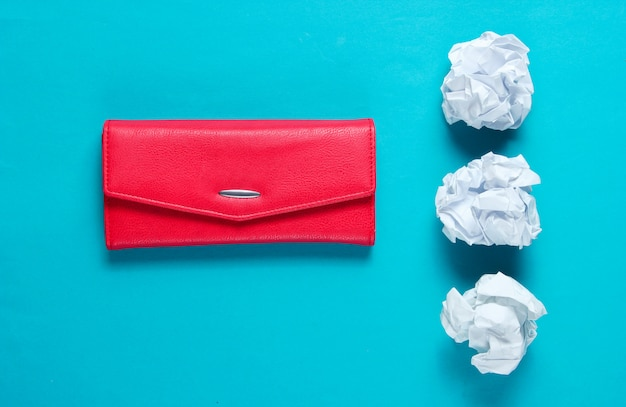Concetto minimale. palle di carta stropicciata, portafoglio in pelle rossa sul tavolo blu Foto Premium