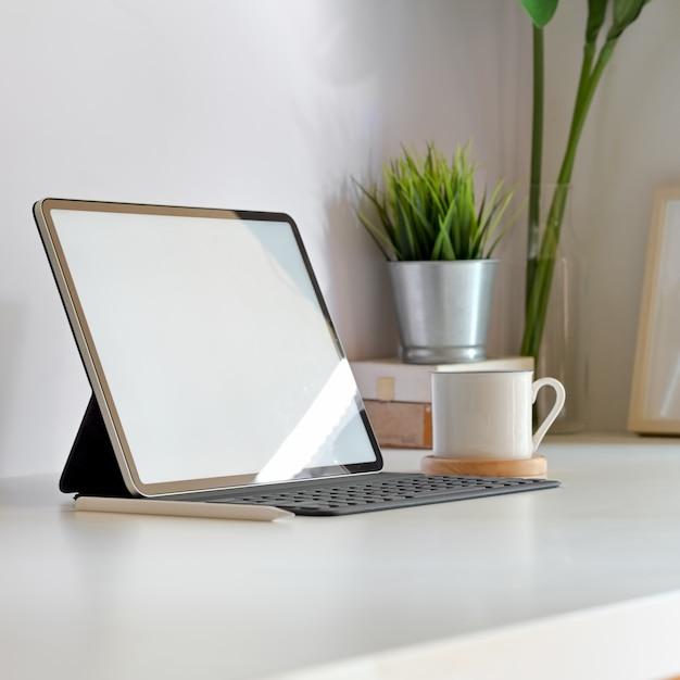 Luogo di lavoro minimo con mockup tablet schermo vuoto Foto Premium
