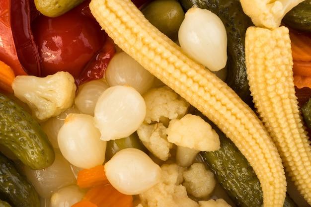 Vista superiore del modello di sottaceti misti. cetriolo marinato, carota, cipolla perl, mais, peperone rosso, cavolfiore, olive e capperi Foto Premium