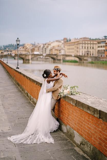 Sposi di razza mista. matrimonio a firenze, italia. la sposa afro-americana e lo sposo caucasico stanno abbracciando sull'argine del fiume arno, con vista sulla città e sui ponti. Foto Premium