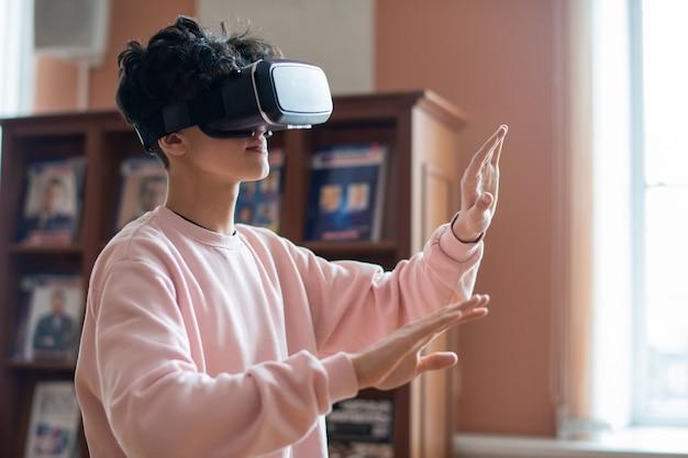 Studente di college mobile in abbigliamento casual e occhiali vr toccando lo schermo virtuale mentre si muove nella realtà tridimensionale Foto Premium