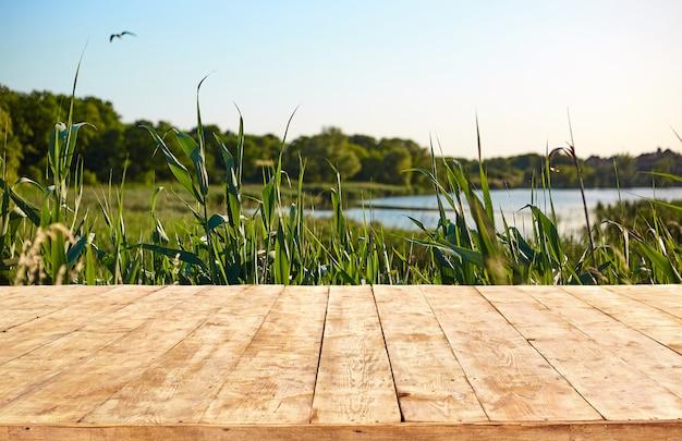 Modello. svuoti la tavola di legno della piattaforma con il fondo del bokeh del fogliame. Foto Premium