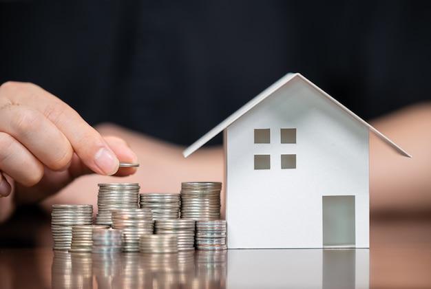 Case modello e monete impilate. prestiti di equità domestica. mutui e prestiti. Foto Premium