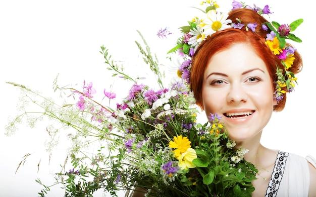 Modello con ampia acconciatura e fiori tra i capelli e con bouquet di fiori. Foto Premium