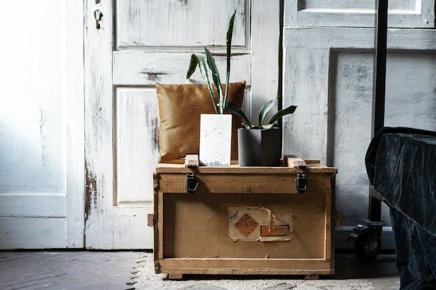 Design moderno del loft interno del soggiorno. pareti in legno grigie con copyspace libero. trend verde in vasi di cemento su una vecchia scatola di legno. Foto Premium