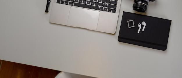 Moderna area di lavoro per i fotografi con laptop mock-up, fotocamera, agenda e copia spazio Foto Premium