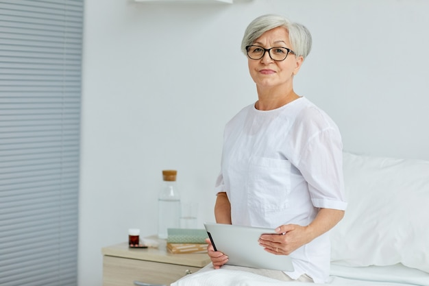Moderna donna senior seduta sul letto in reparto ospedaliero tenendo la tavoletta digitale Foto Premium