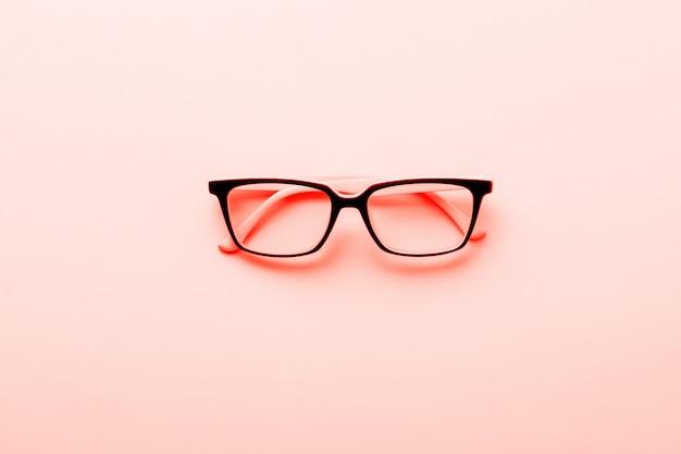Occhiali moderni occhiali isolato su sfondo giallo. colore di corallo vivente alla moda dell'anno 2019. vista dall'alto. Foto Premium