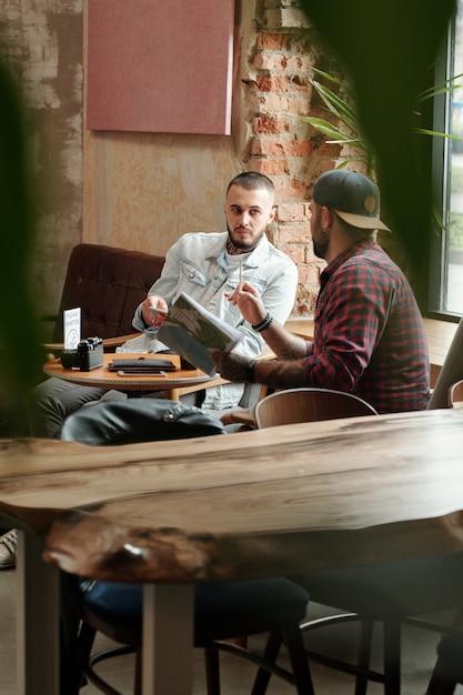 Giovani moderni seduti a tavola in un caffè vuoto e scambiano idee per scattare foto insieme Foto Premium