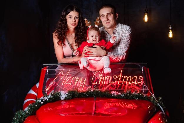 Mamma, papà e neonata che si divertono nella retro automobile rossa di natale. genitori con una piccola figlia in una sessione fotografica di natale. Foto Premium