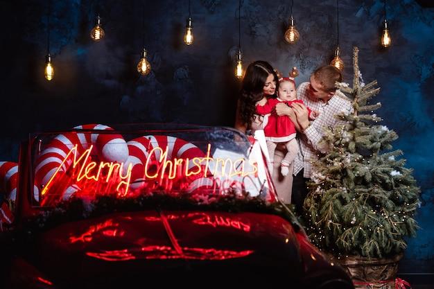 Mamma, papà e neonata divertendosi vicino all'albero di natale e alla retro automobile rossa. genitori con una piccola figlia in una sessione fotografica di natale. Foto Premium