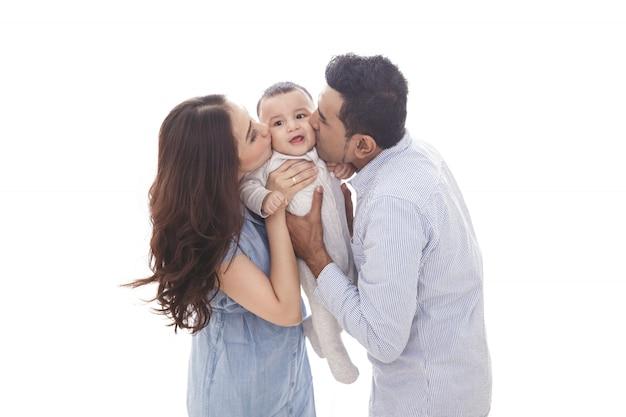 Mamma e papà baciano il loro bambino carino Foto Premium