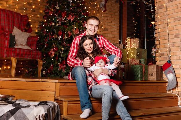 Mamma e papà posano con la loro piccola figlia affascinante nello studio di natale decorato. sessione fotografica di capodanno. Foto Premium