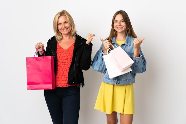 Mamma e figlia che comprano alcuni vestiti isolati sulla parete bianca che dà un pollice in alto gesto con entrambe le mani e sorridente Foto Premium
