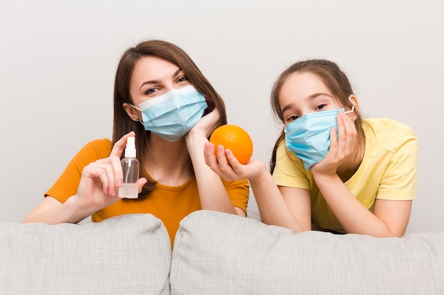 Mamma e ragazza con maschera e frutta Foto Premium