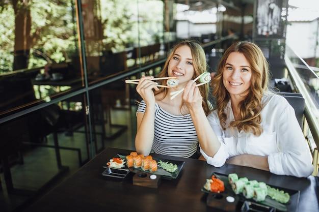 La mamma e la sua giovane e bella figlia mangiano sushi con bastoncini cinesi. Foto Premium