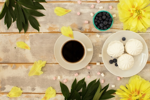 Caffè del mattino, marshmallow e bellissimi fiori gialli di peonia Foto Premium