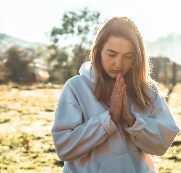 Al mattino la ragazza chiuse gli occhi, pregando all'aperto, le mani giunte nel concetto di preghiera per la fede, la spiritualità e la religione. pace, speranza, concetto di sogni. Foto Premium