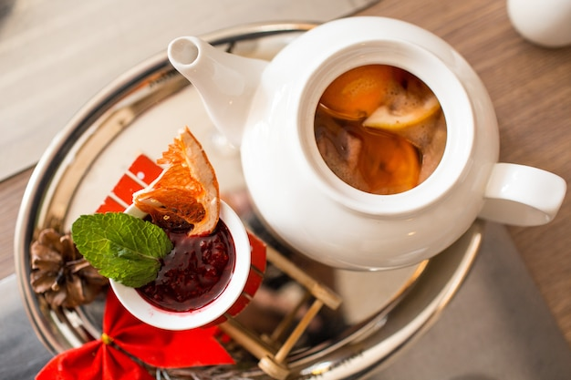 Tè marocchino con arancia e limone in una teiera con marmellata di lamponi e spezie Foto Premium
