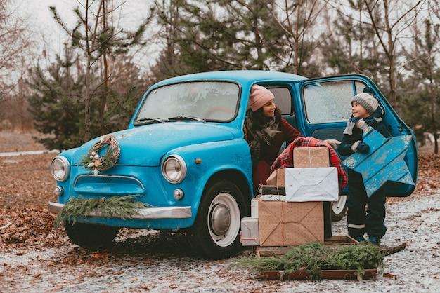 Madre e figlio decorato con auto retrò blu con rami di un albero di natale festivo, scatole regalo, carta da regalo artigianale, aghi di pino e abete ghirlanda. viaggio di famiglia di capodanno. sogno d'infanzia, desideri di ricordi. Foto Premium