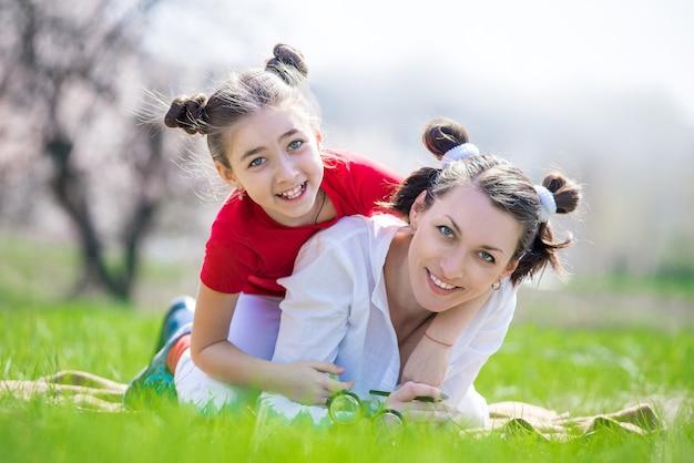 Madre e figlia che camminano nel giardino in primavera Foto Premium