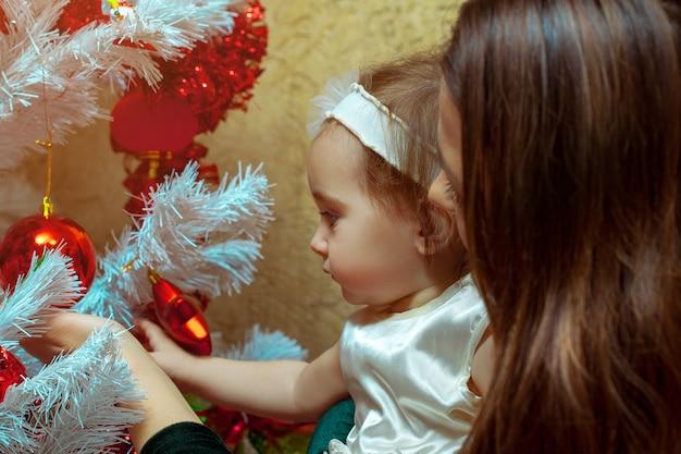 La mamma decora l'albero di natale con la sua piccola bambina Foto Premium